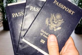Hand holding three US Passports - two passports at once - GreatDistances / Matt Wicks
