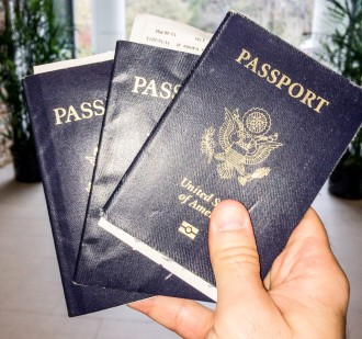 Hand holding three US Passports - two passports at once - GreatDistances / Matt Wicks