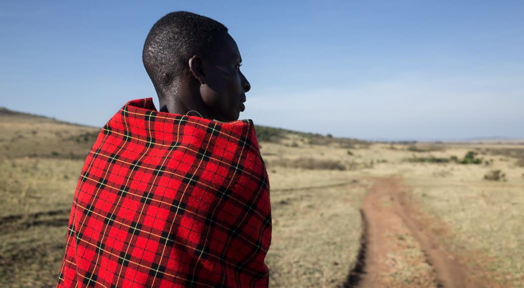 Maasai guide surveys the Maasai Mara just inside Sekenani Gate. GreatDistances / Matt Wicks