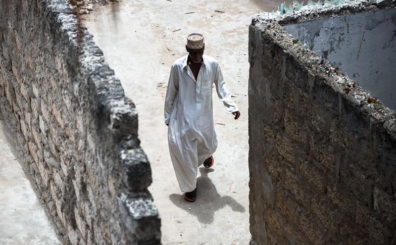 A Muslim man walks in the alleyways of Lamu. GreatDistances / Matt Wicks