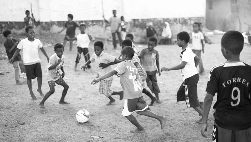 Frenzied moves toward goal - boys play an intense game of soccer/futbol in a dirt lot with a flattened ball in Lamu, Kenya. GreatDistances / Matt Wicks