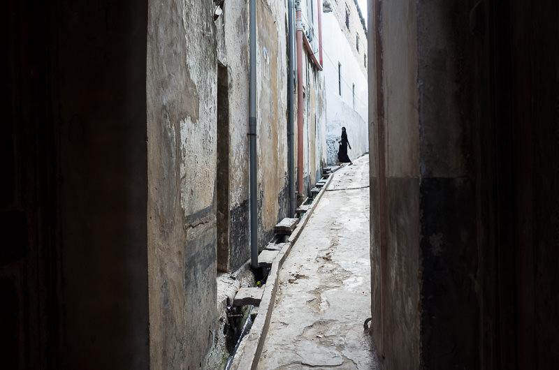 Obscured view of a woman in Lamu Town's alleyways.  GreatDistances / Matt Wicks