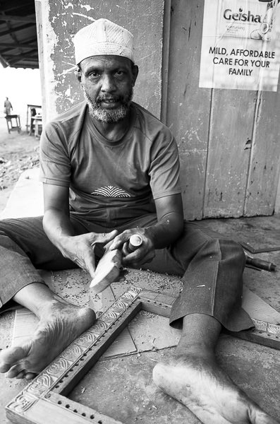 Hassan of Lamu Town, carving patterns into furniture by hand with a chisel.  GreatDistances / Matt Wicks
