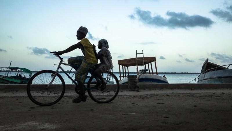 Children take a late afternoon bike ride on Lamu Town's waterfront.  GreatDistances / Matt Wicks