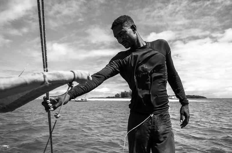 spear fisherman takes in the sun and breeze on a dhow outside Lamu, Kenya. GreatDistances / Matt Wicks