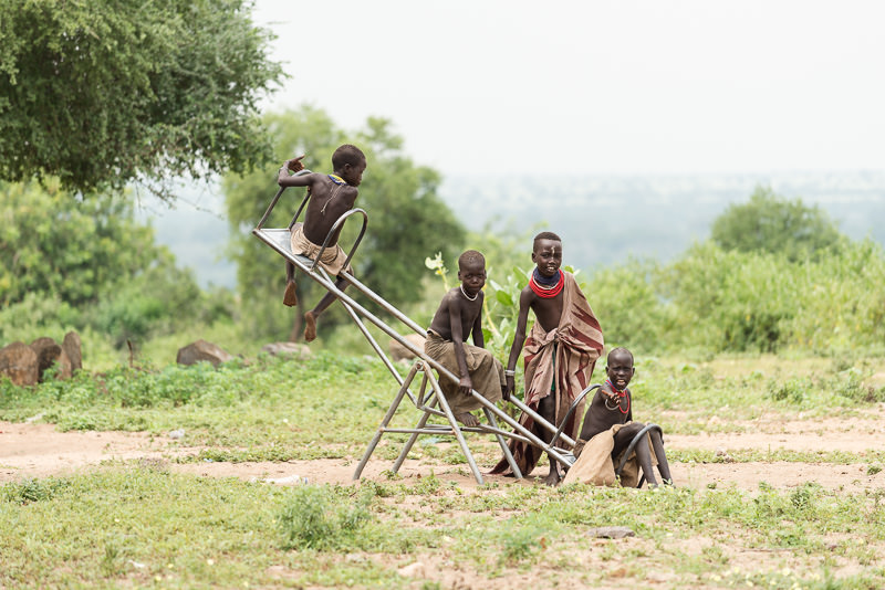 Karo tribe boys on a see-saw in the village of Kolcho. Photographing the Tribes of South Omo, Ethiopia - GreatDistances / Matt Wicks