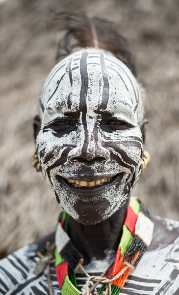 An oft-photographed male member of Karo tribe in full face paint. Photographing the Tribes of South Omo, Ethiopia - GreatDistances / Matt Wicks