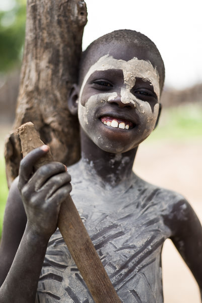 Real smile from a young painted boy from the Karo tribe. Photographing the Tribes of South Omo, Ethiopia - GreatDistances / Matt Wicks