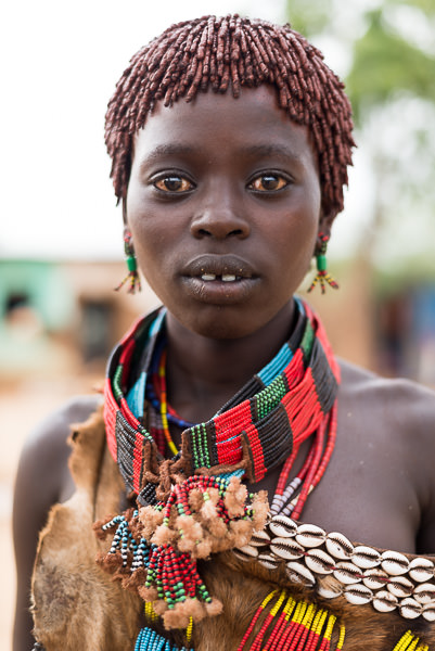 Hamar woman in goatskin, beads, puka shells and ochred hair. Photographed in Turmi. How To Visit South Omo, Ethiopia (Omo Valley) - GreatDistances / Matt Wicks