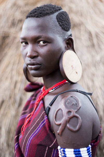 Mursi woman with stretched earlobes and scarification. Photographing the Tribes of South Omo, Ethiopia - GreatDistances / Matt Wicks