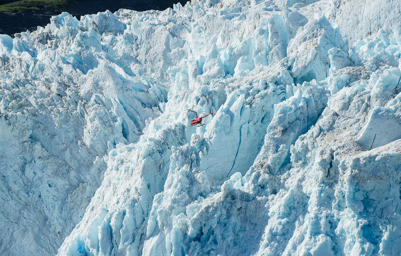 A helicopter flies near the edge of the massive Aialik Glacier, a tidewater glacier in Kenai Fjords National Park. GreatDistances / Matt Wicks - Two Weeks in Alaska: Selected Photos
