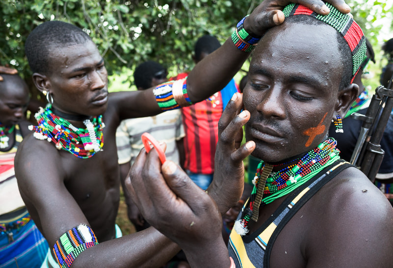 Men from Hamar tribe apply natural paints to one anothers' faces at a bull jumping ceremony. Photographing the Tribes of South Omo, Ethiopia - GreatDistances / Matt Wicks