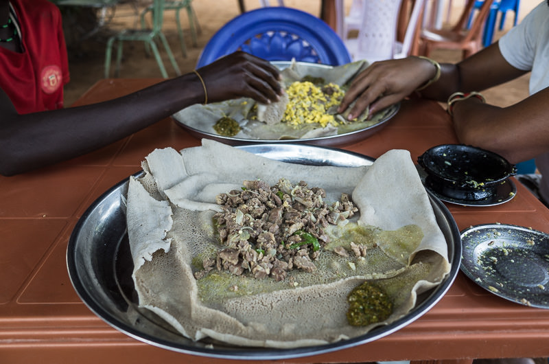 Ethiopian food: Injera and goat tibs in Turmi, South Omo, Ethiopia. How To Visit South Omo, Ethiopia (Omo Valley) - GreatDistances / Matt Wicks